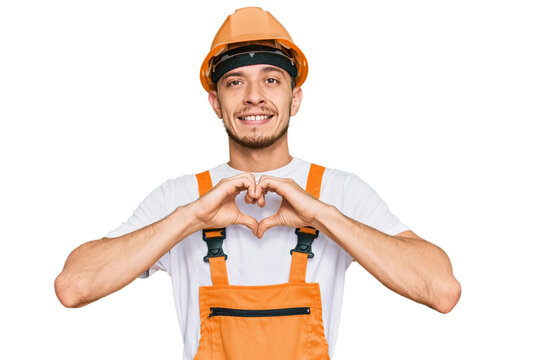 Hispanic young man wearing handyman uniform and safety hardhat smiling in love showing heart symbol and shape with hands. romantic concept.