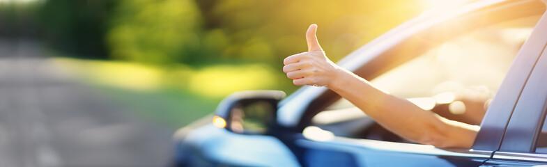 Woman inside her car gesticulate thumb up - fototapety na wymiar