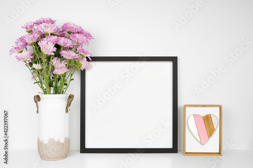 Mock up black frame with vase of purple mum flowers and heart decor. Mother's Day decor theme. White shelf against a white wall. Copy space.