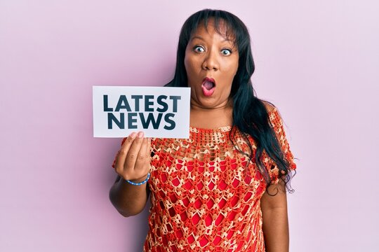 Middle age african american woman holding latest news message on paper scared and amazed with open mouth for surprise, disbelief face
