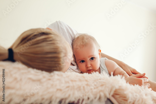 Woman lying on bed with her baby. Mother hugging kid. Family relaxing at home. Mother's day