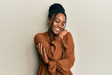 Fototapeta African american woman with braided hair wearing casual brown shirt hugging oneself happy and positive, smiling confident. self love and self care obraz