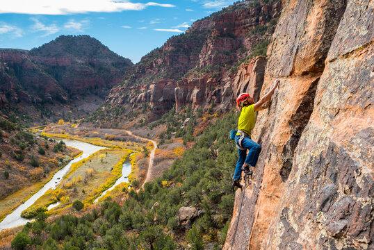 A man rock climbing in the Dolores River Canyon, Dove Creek, Colorado.