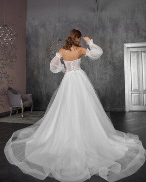 Full length bride portrait. Elegant female model wearing white fluffy wedding dress, standing and posing in grey room.