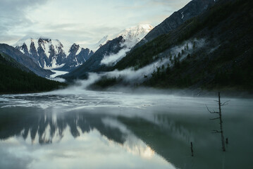 Scenic alpine landscape with snowy mountains in golden sunlight reflected on mirror mountain lake in fog among low clouds. Atmospheric highland scenery with low clouds on rocks and green mirror lake.