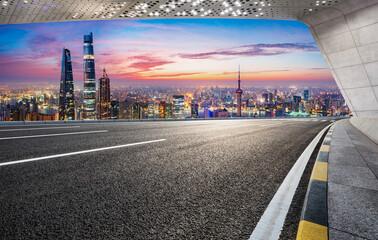 Asphalt road and city skyline at sunrise in Shanghai.