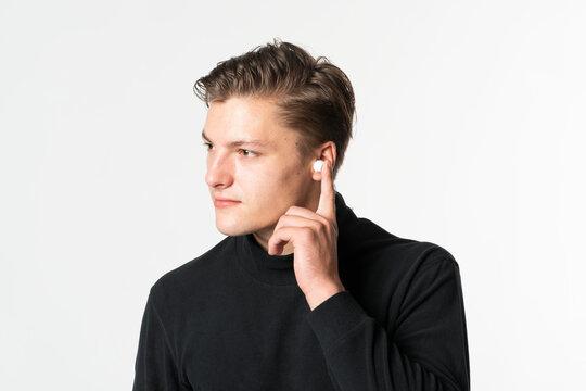 Man touching wireless earbuds communication technology