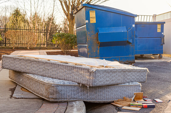 Despite regulations by the Home owners association, residents still illegally dump bulk items by the residential trash containers. Two old mattresses left behind by dumpster create unsightly look.