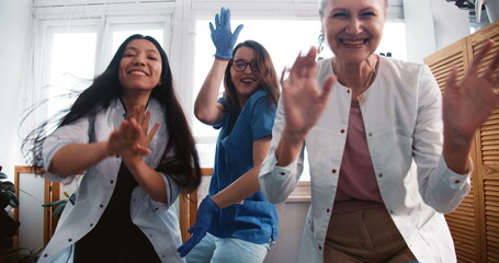 End of fighting coronavirus. Zoom out three fun multiethnic happy female doctors dancing together at clinic lab office.