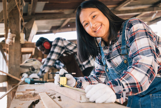 Carpenter woman using tools for wood of his own housing with assistant at work site. Carpenter makes facade details for construction. housekeeping maintenance concept.