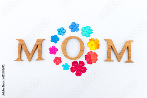 Mother's day card background idea,  wooden font arrangement in mom word with colorful paper flower isolate on white background