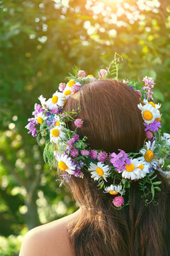 girl in summer solstice wreath, sunny day outdoor. rear view of woman with brown hair and wildflowers wreath. pagan Slavic ceremony on Midsummer