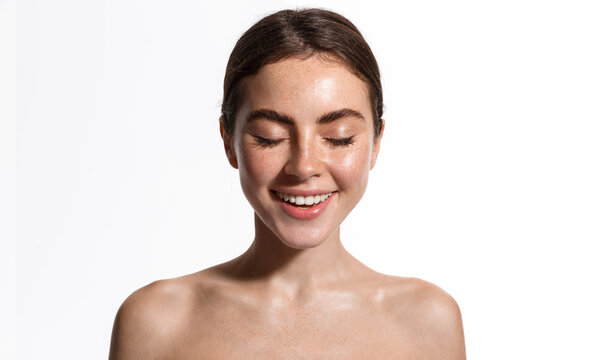 Beauty skin of young natural model with freckles, eyes closed. Girl trying new cosmetics, standing with naked shoulders, using facial toners and sunscreen spf nude makeup, white background