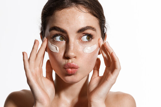 Close up beauty girl with freckles and thick eyebrows, applying moisturizing skincare cream, lotion or mask for skin lifting and anti-aging detoxifying effect, white background