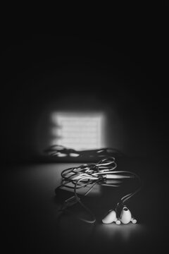 Black and white image of a pair of white wired ear buds on top of a mobile smart phone