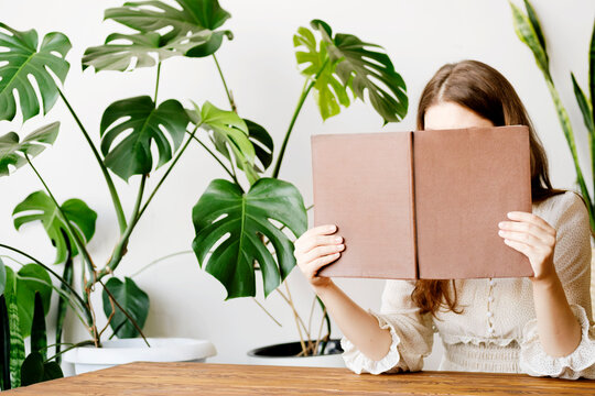 A woman in a light silk dress in a reading room with monstera plants holds a book next to her face