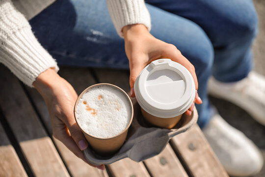 Woman with takeaway cups of tasty latte outdoors, closeup