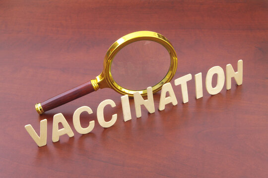Magnifying glass and word vaccination on wooden table. Review of vaccination concept.