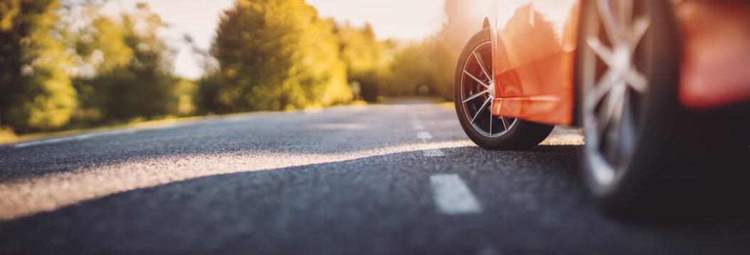 Red car on asphalt road in summer