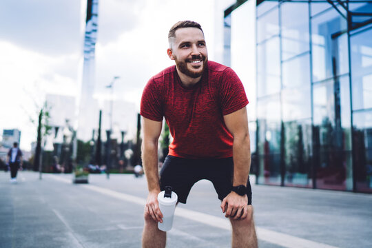 Cheerful sportsman resting after workout on pavement