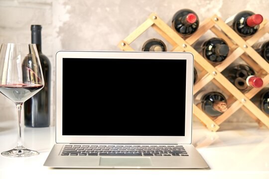 Empty blank screen laptop computer on table with wine bottle wine rack holder in the background. Buying wines online, home delivery concepts.