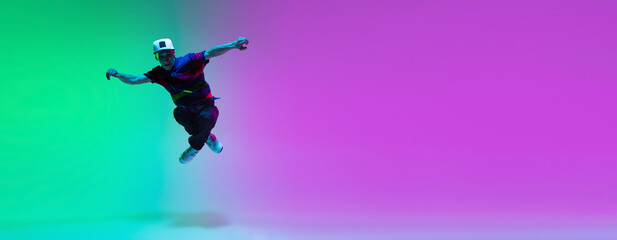 Beautiful sportive boy dancing hip-hop in stylish clothes on colorful gradient background at dance hall in neon light.