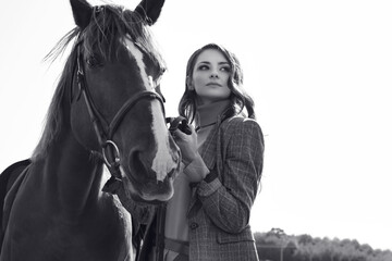 Fototapeta Portrait of a gorgeous brunette woman in an elegant checkered brown jacket posing with a horse on country landscape
