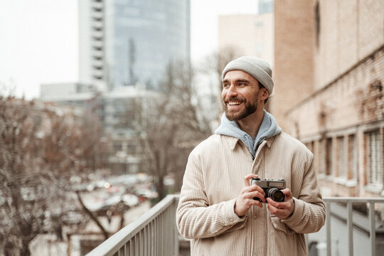 bearded man in beanie hat and jacket smiling while holding retro camera