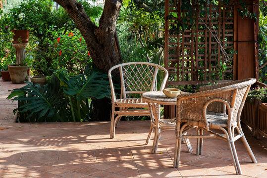 Terrace with comfortable wicker furniture, villa in garden, Sicily, Italy