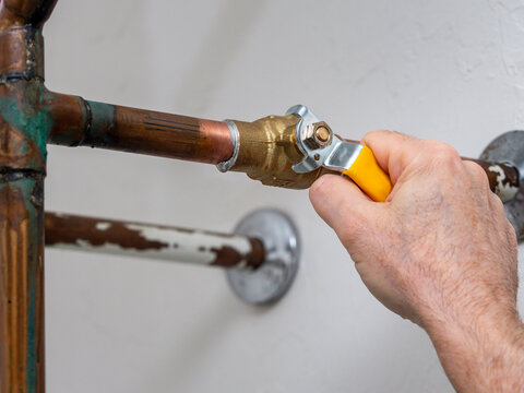 Plumber turning water shut off valve. Copper plumbing pipe with brass water supply valve and yellow stopcock handle.