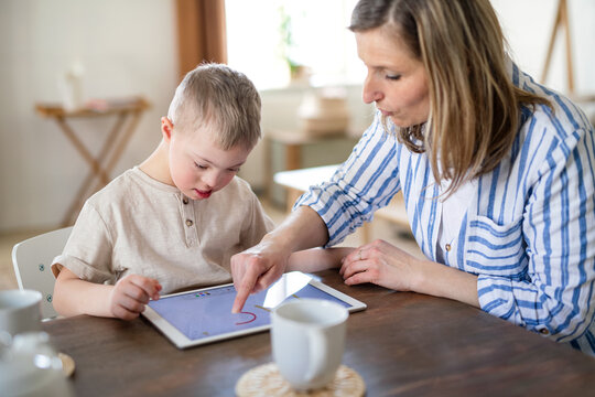 Single mother with down syndrome son with tablet at home, distance learning.