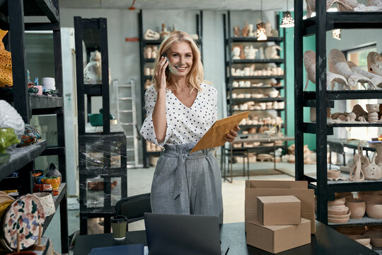 Successful mature business woman, shop owner smiling at camera, talking on the phone, holding envelope while checking mail, standing in her craft pottery shop