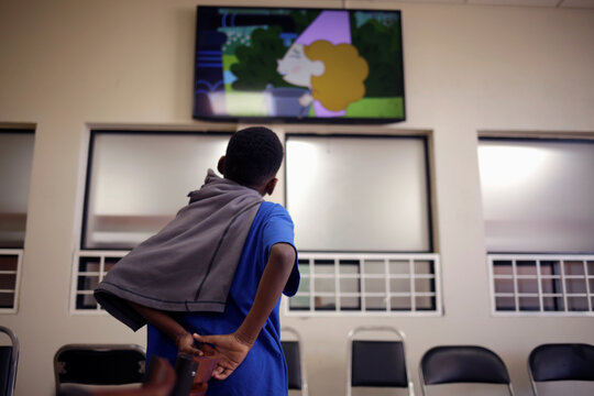 A migrant child from Central America watches television at the Noemi Alvarez Quillay immigrant shelter for unaccompanied minors, run by the Mexican government, in Ciudad Juarez