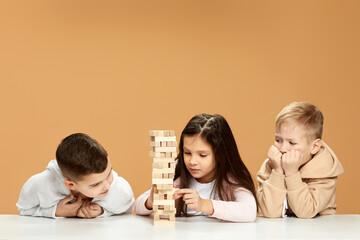 Fototapeta children plays with wooden constructor on desk.