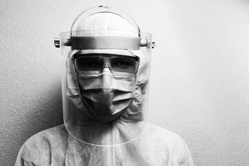 Black and white portrait of a doctor wearing PPE suit against coronavirus and covid-19, on the...