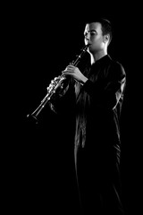 Clarinet player classical musician isolated on black. Clarinetist playing music instrument