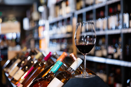 Closeup of red wine glass on blurred background with shelves in wine shop