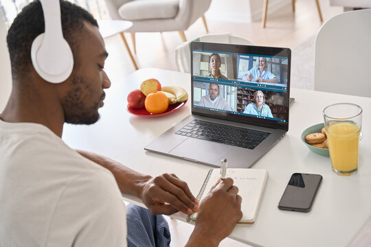 African Black business man having virtual team meeting on video conference call using laptop distance working from home office with diverse people group in team online remote chat. Over shoulder view