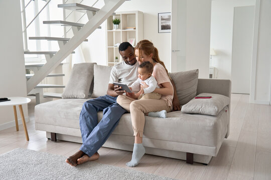 Happy young multi ethnic diverse parents having fun using digital tablet computer holding cute little mixed race baby child daughter sitting on couch in modern cozy living room at home together.