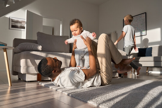 Happy African American father holding cute adorable little child daughter lying on floor enjoying sweet moments. Smiling affectionate Black dad playing having fun with infant kid baby girl at home.
