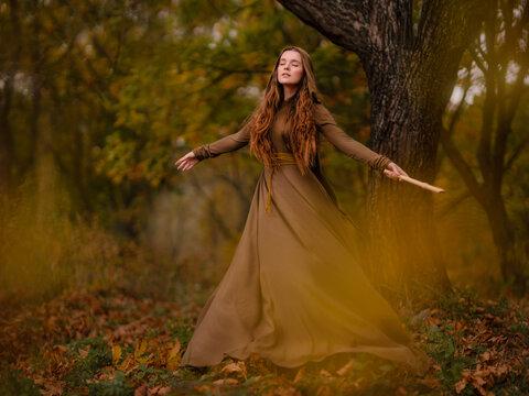 Redhead woman in dress walking in fantasy fairy tale forest