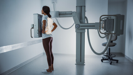 Hospital Radiology Room: Beautiful Multiethnic Woman Standing in the X-Ray Machine. Adult Female...