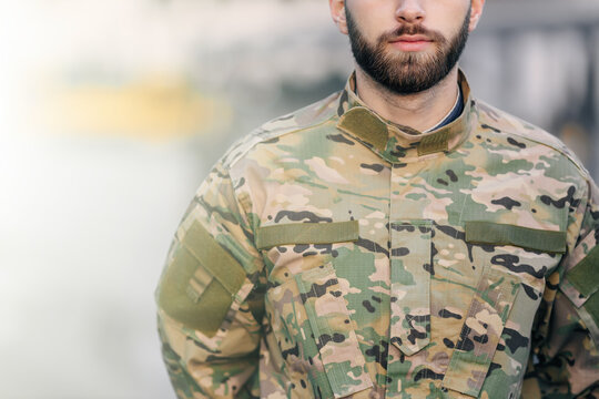 cropped shot of a bearded military man holding his hands behind his back, in camouflage on the street