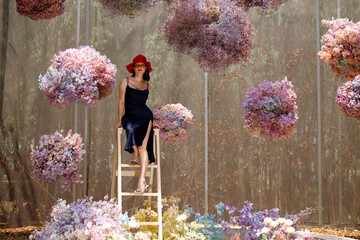 Woman walk in Fantasy Flower Dream Field with beautiful color