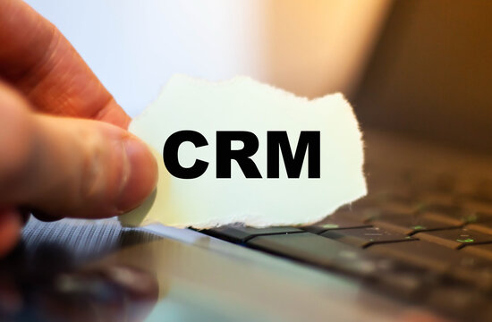 CRM customer relationship management. Word on paper in the hands of the sales manager