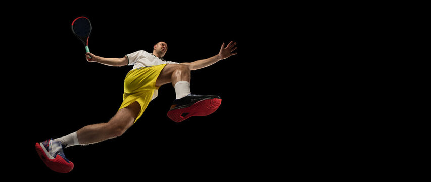 Young caucasian tennis player in action, motion isolated on black background, look from the bottom. Concept of sport, movement, energy and dynamic.