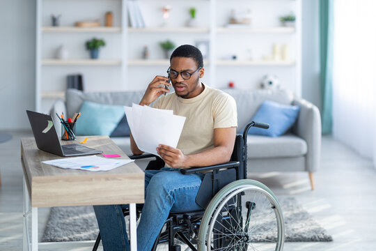 Online work for disabled people. Young black guy with documents speaking on phone in front of laptop at home