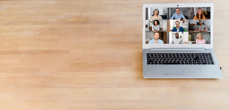 A laptop with a many people profile on it on the wooden table, video call, video conference, online video meeting of multiracial team. Copy space