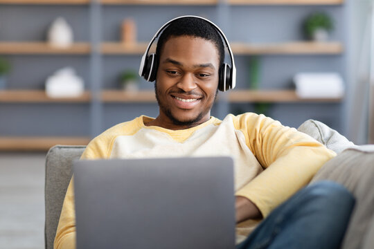 Closeup of happy black guy playing video games on laptop