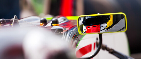 A view of a driver in the rearview mirror inside his supercar and ready to start the race